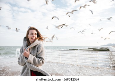 Smiling beautiful young woman standing on pier in winter