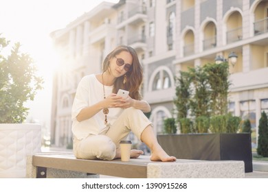 Smiling beautiful young woman using smartphone while resting on wooden bench in city street in summer outdoor.
