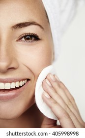 Smiling beautiful young woman using face scrub