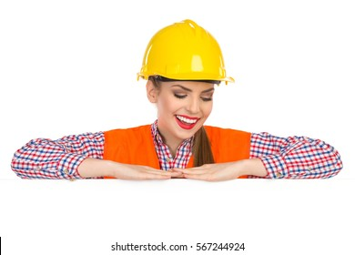 Smiling beautiful young woman in yellow hardhat, orange reflective vest and lumberjack shirt leans on a banner, and looking down on a white copy space. Head and shoulders studio shot isolated on white