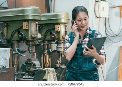 smiling beauty female milling machine factory manager holding pad computer standing in workplace and using mobile cell phone calling for client confirming order.