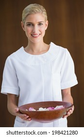 Smiling beauty therapist holding bowl of rose petals at the spa