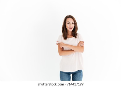Smiling beauty woman with crossed arms pointing away and looking at the camera over white background