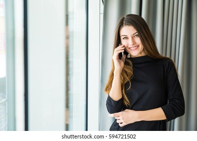 Smiling beauty woman talking on phone in office
