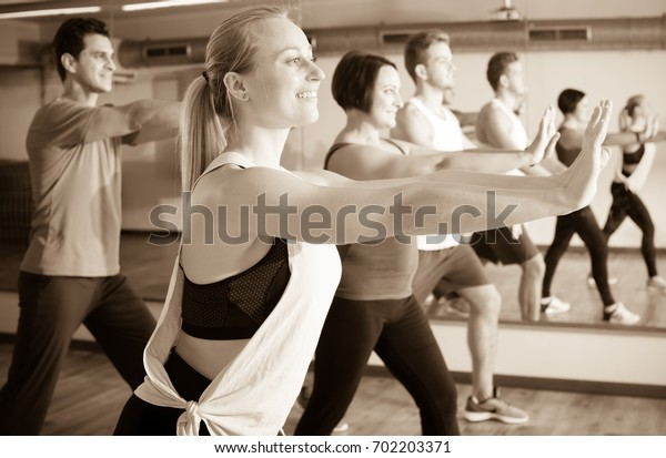 Smiling beginner people learning zumba elements together in dancing class