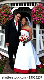 Smiling bi-racial bridal couple with red highlights