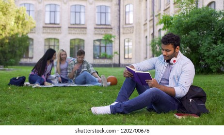 Smiling biracial male student sitting on grass and reading interesting book