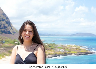 Smiling biracial teen girl or young woman stading with blue Hawaiian sea in background
