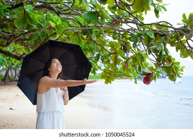 Smiling biracial woman in white dress holding black umbrella in rain on Hawaiian beach, hand stretched out to feel rain