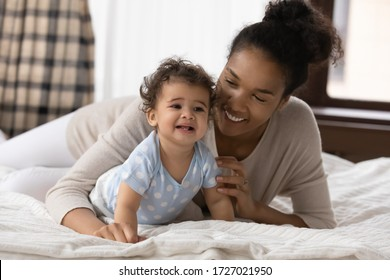 Smiling biracial young mother lying relaxing on bed at home creeping with small toddler infant child, happy african American mom rest in bedroom, playing with little baby, childcare, family concept