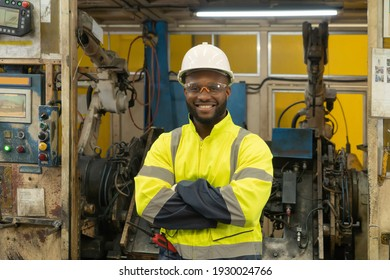 Smiling black African American man, an engineer or worker with the smart robot welding hand system automated manufacturing machine engine in factory, industry equipment in operation warehouse. People.