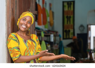 Smiling black African woman in traditional clothes wishing welcome to customers in front of her store