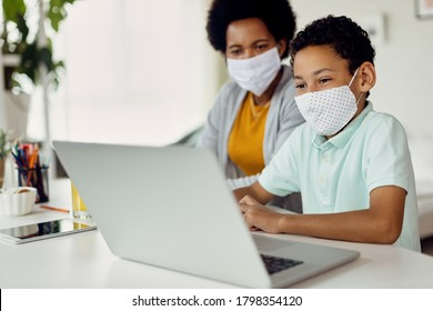 Smiling black boy using laptop and e-learning with help of his mother at home during coronavirus epidemic.
