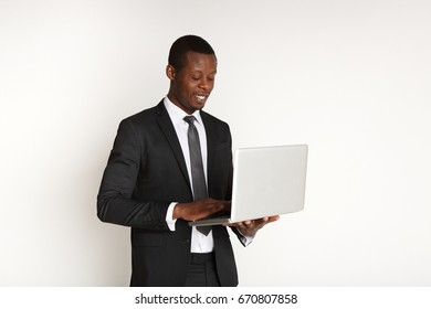 Smiling black businessman with laptop isolated. Young man in suit working on computer while standing up, white background. Portable device. e-commerce, business concept