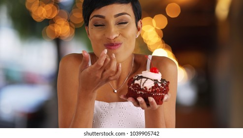 Smiling black female eating fancy cupcake in outdoor setting with bokeh lights
