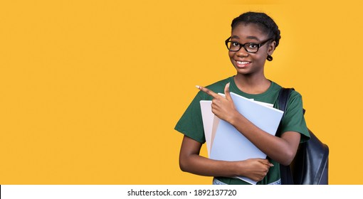 Smiling Black Female Student Pointing Finger Aside At Empty Space For Text Posing With Books And Notebooks Standing Over Yellow Studio Background. Great Educational Offer Advertisement