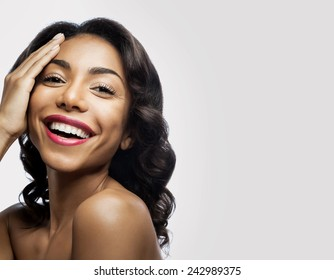 Smiling black girl with perfect healthy skin and makeup. As for the hand of his face on a gray background
