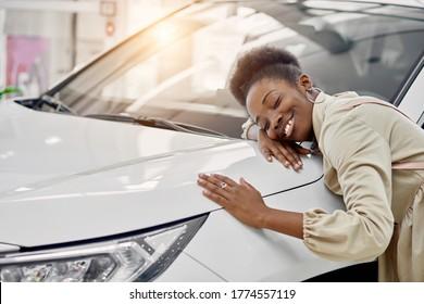 Lächelnde schwarze Dame umarmt ihr neues Auto in Autos Showroom. junge Frau erfüllt ihren Traum, lügt auf dem Auto