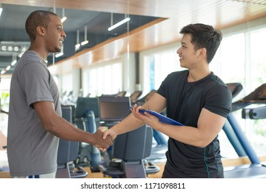 Smiling black man thanking personal trainer in gym. Young guy greeting instructor with gym equipment in background. Personal trainer concept.