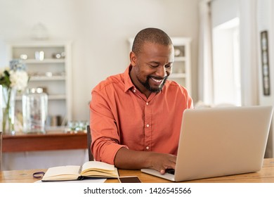 Smiling black man using laptop at home in living room. Happy mature businessman send email and working at home. African american freelancer typing on computer with paperworks and documents on table.