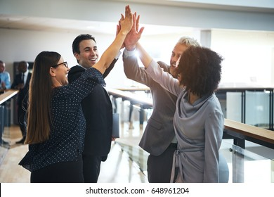 Smiling black and white business people standing in office and giving high five during teambuilding.