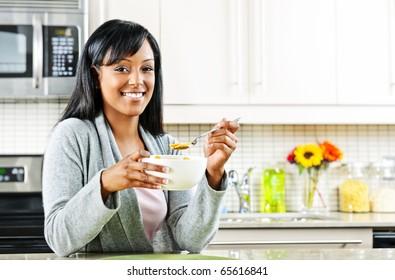 Smiling black woman having breakfast in modern kitchen interior