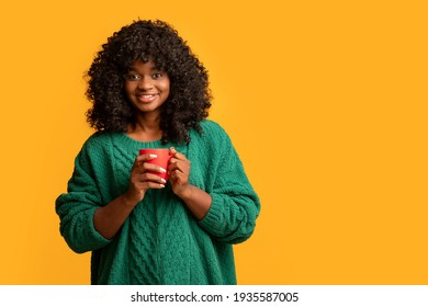 Smiling black woman holding red mug, drinking coffee