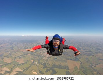 Smiling black woman jumping from parachute