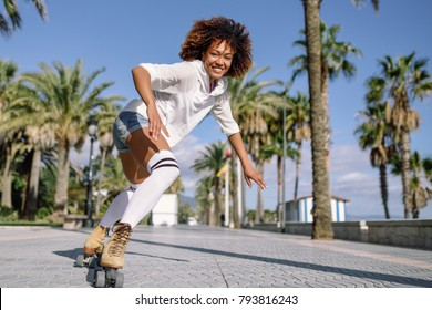 Smiling black woman on roller skates riding outdoors on beach promenade with palm trees.