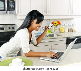 Smiling black woman online shopping using computer and credit card in kitchen