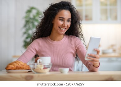 Smiling black woman using smartphone while having breakfast in kitchen at home, cheerful african american female sitting at table, reading text messages on her cell phone and eating food, free space