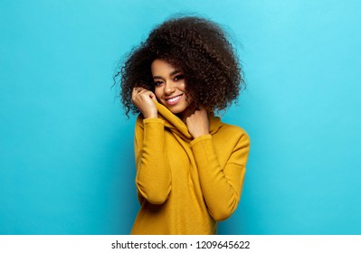 Smiling black woman wear cardigan isolated on blue background