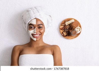 Smiling black woman with white mask on half face and aromatherapy plate on white background, top view