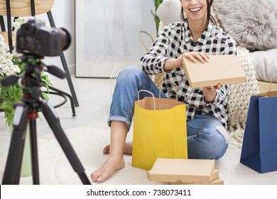 Smiling blogger recording herself unboxing gifts from subscribers
