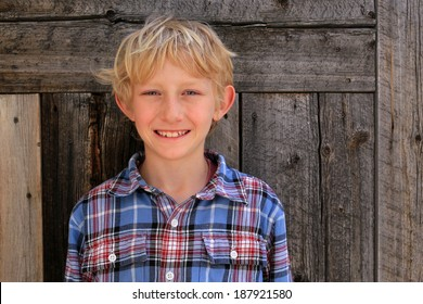Smiling blond boy with a barn wood background.