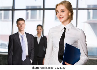 Smiling blond Caucasian woman holding blue paper case and two walking businesspeople on the background
