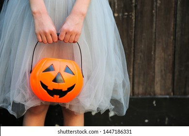 Smiling blond girl holding Halloween pumpkin jack o'lantern with sweet candy in hands on wooden background. Halloween celebration concept