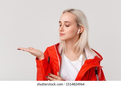 Smiling blond girl with wireless earbuds wearing red raincoat with hood pointing finger at empty space on a palm of a hand isolated over white background. Place for advertising