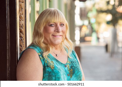 Smiling blond middle aged transgender lady in blond hair and green top