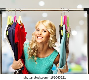 Smiling blond woman choosing clothes on a rack in a shopping mall
