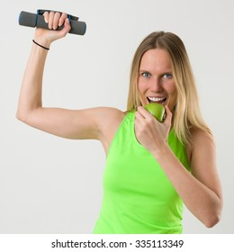 Smiling blond woman doing exercises with dumbbells and biting an green apple