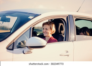 Smiling blond woman driving a car on a sunny summer day viewed through her open side window