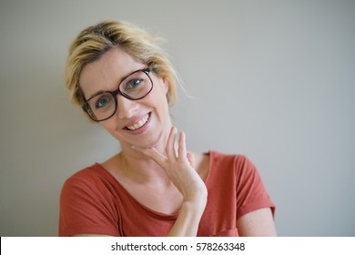 Smiling blond woman with eyeglasses and red shirt,  isolated