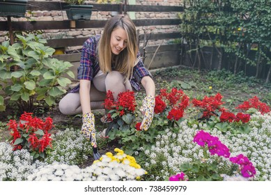 2a190c77 Smiling blond woman gardening. Young pregnant woman gardening outside and  holding flowers. gardener cutting