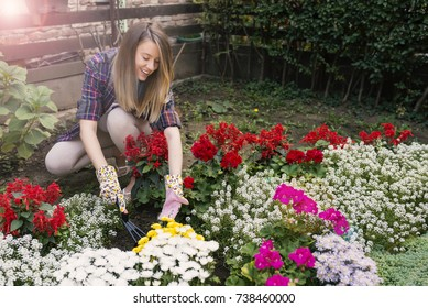 f77d7ef8 Smiling blond woman gardening. Young woman gardening outside and holding  flowers. gardener cutting little