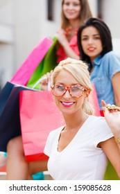 Smiling blond woman with her friends out shopping.
