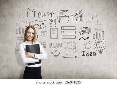 Smiling blond woman hugging her black folder is standing near a concrete wall with a business idea sketch on it