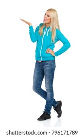 Smiling blond woman in turquoise hoodie and jeans is standing with hand raised, presenting something, looking away and talking. Full length studio shot isolated on white.