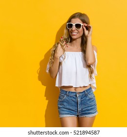 Smiling blond young woman in jeans shorts, white shirt and sunglasses posing and looking away, Three quarter length studio shot on yellow background.
