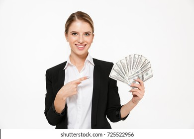 Smiling blonde business woman holding money and pointing on their while looking at the camera over white background